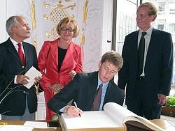 Paul Ferguson trägt sich ins Goldene Buch der Stadt ein, rechts: Jim Rowland (neuer Vorsitzender des Arlington-Aachen-Komitees), (c) Stadt Aachen / Paul Heesel